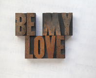 Wood type words be my love. The words 'be my love' in old wood type on a faded sheet music background Royalty Free Stock Photo
