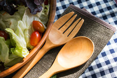Wood Utensils. With salad bowl on the checkered tablecloth Royalty Free Stock Photos