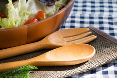 Wood Utensils. With salad bowl on the checkered tablecloth Stock Images