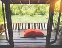 Wood uteplats på ett avslappnande grönt damm med matt bambu och kuddar Arkivfoton