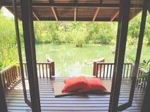 Wood uteplats på ett avslappnande grönt damm med matt bambu och kuddar Royaltyfria Bilder