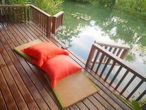 Wood uteplats på ett avslappnande grönt damm med matt bambu och kuddar Royaltyfri Foto