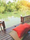 Wood uteplats på ett avslappnande grönt damm med matt bambu och kuddar Arkivbild
