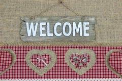 Wood välkommet tecken med den röda plädgränsen med hjärtor på säckvävbakgrund Royaltyfria Bilder