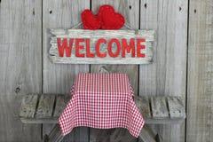 Wood välkommet tecken med hjärtor över picknicktabellen Royaltyfri Foto