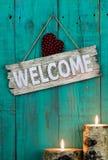 Wood välkommet tecken med röd hjärta av levande ljus som hänger på antik krickablåttbakgrund Royaltyfri Bild