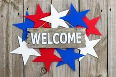 Wood välkommet tecken som omges av röda, vita och blåa stjärnor Royaltyfri Bild