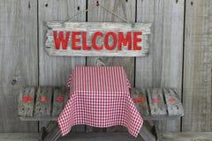 Wood välkommet undertecknar över picknicktabellen Fotografering för Bildbyråer