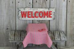 Wood välkommet undertecknar över picknicktabellen Arkivbilder
