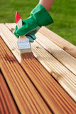 Wood varnishing. Applying protective varnish on a patio wooden floor Stock Photos