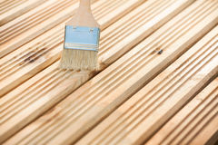Wood varnishing. Paint brush on a wooden background Royalty Free Stock Photography