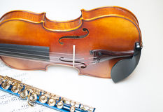 Wood violin body part with blue flute and score. Wood violin body part detail with strings and f-hole, and blue flute part on score Stock Image