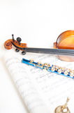 Wood violin detail with blue flute and score. Wood violin neck detail with out of focus blue flute and score Royalty Free Stock Image