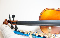 Wood violin detail with blue flute and score. Wood violin neck detail with out of focus blue flute and score Royalty Free Stock Photos