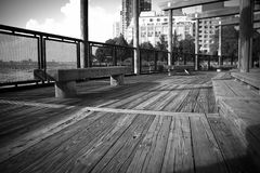 Wood walkway and bench next to the water in black and white Royalty Free Stock Photography