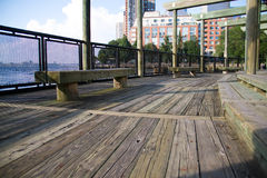 Wood walkway and bench next to the water Royalty Free Stock Photo