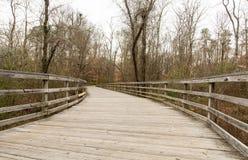 Wood Walkway Curving Through Winter Woods Stock Photos