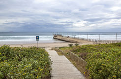Wood Walkway onto Beach with Pier Leading into Sea Royalty Free Stock Photos