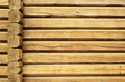 Wood wall of a loghouse. A wood wall is made of logs uncolored. This is the timber background of weathered beams with deep cracks Royalty Free Stock Photos