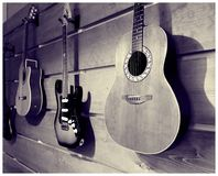 Wood Wall of Mounted Guitars on Display. Wall of mounted guitars on display. Hanging guitars include acoustic and electric instruments royalty free stock photography