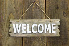 Wood welcome sign hanging on rustic wooden background Stock Images