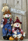 Wood welcome sign hanging on wooden fence by boy and girl scarecrows. Boy and girl scarecrow rag dolls by wood welcome sign hanging on rustic wooden fence Stock Image
