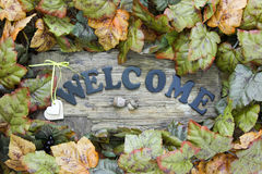 Wood welcome sign with hearts and autumn leaves border hanging on door Royalty Free Stock Photo