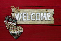 Wood welcome sign with plaid country Christmas hearts hanging on dark red wood background Royalty Free Stock Photos