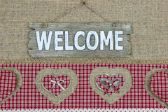 Wood welcome sign with red plaid border with hearts on burlap background Royalty Free Stock Images