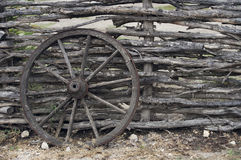 Wood wheel from cart on the wood fence Stock Image