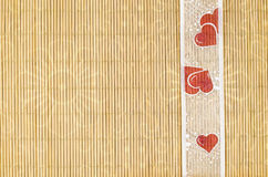 Wood, wicker background with flower motif and heart ribbon Stock Photos