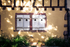 Wood window shutter with cutout clubs. Summer, Alsace, France Stock Images
