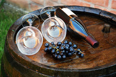 Wood Wine barrel. Glasses and bottle of wine lying over wooden barrel Royalty Free Stock Images