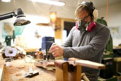Wood worker building guitar in his shop, using a plunge router stock image