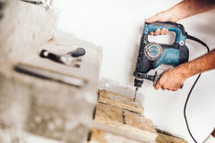 Wood worker using professional drill press for making holes in wood boards and concrete. Precise wood worker using professional drill press for making holes in Stock Image