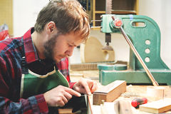 Wood Working Luthier Building a Guitar in his Workshop. A young man who works as a luthier is building a wood acoustic guitar in his home workshop Stock Photo