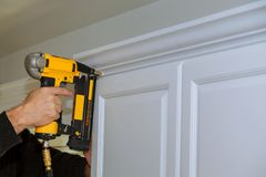 Free Wood Working Using Brad Nail Gun To Crown Moulding On White Kitchen Cabinets Framing Trim, Stock Images - 106615484
