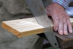 Wood workshop. carpenter cutting plank with hand saw Royalty Free Stock Photography