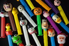 Colorful Pez Dispensers. WOODBRIDGE, NEW JERSEY / UNITED STATES: May 12, 2019: Colorful Pez dispensers from the 1980s and 1990s are seen against a black royalty free stock photos