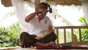 Woodcarver που κάνει τη χάραξη με τα αιχμηρά εργαλεία στο ξύλινο κομμάτι προς κατεργασία Παραδοσιακή από το Μπαλί statuette κάνον φιλμ μικρού μήκους