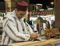 Woodcarver artisan in national clothes in the pavilion of Turkey Royalty Free Stock Images