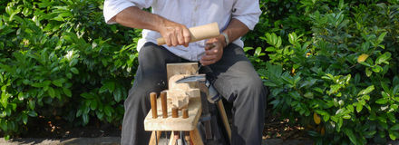 Woodcarver close up. Woodcarver at work in the tradicional market Royalty Free Stock Photos