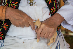 Woodcarver dressed in folk costume carves from wood. Folk art Royalty Free Stock Photography