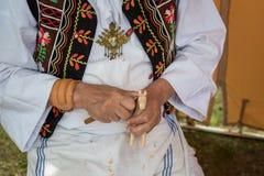 Woodcarver dressed in folk costume carves from wood. Folk art Stock Image