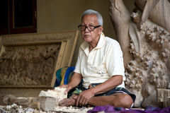 Woodcarver with his artworks of wood Royalty Free Stock Photography