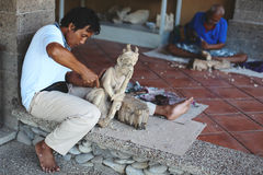 Woodcarver with his artworks of wood posing in local shop Royalty Free Stock Photo