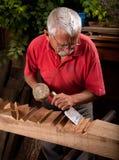 Woodcarver idoso que trabalha com malho imagem de stock