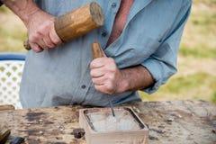 Woodcarver idoso que trabalha com malho e chiesel Imagens de Stock