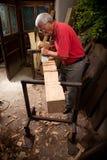 Woodcarver que trabalha com malho e formão Fotografia de Stock