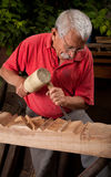 Woodcarver que trabalha com malho e formão Foto de Stock